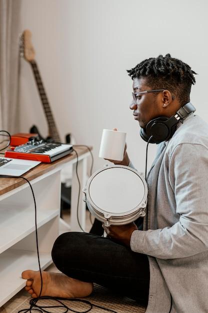 Vue Latérale Du Musicien Masculin à La Maison à Jouer De La Batterie Et à Mélanger Avec Un Ordinateur Portable Photo gratuit