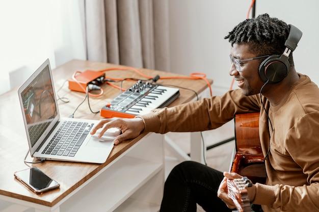 Vue Latérale Du Musicien Masculin à La Maison à Jouer De La Guitare Et à Mélanger Avec Un Ordinateur Portable Photo gratuit
