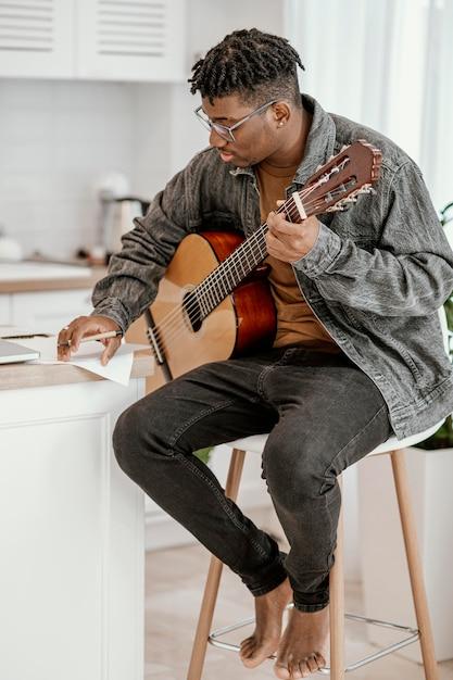 Vue Latérale Du Musicien Masculin à La Maison à Jouer De La Guitare Photo gratuit