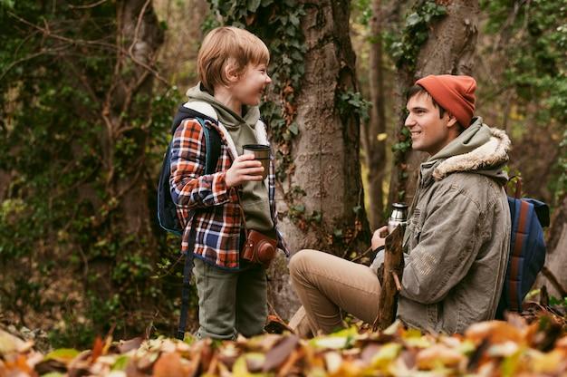 Vue Latérale Du Père Et Fils Ayant Du Thé Chaud à L'extérieur Dans La Nature Photo Premium