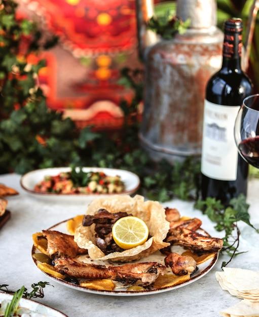 Vue Latérale Du Poulet Rôti Servi Avec Du Vin Sur La Table Photo gratuit