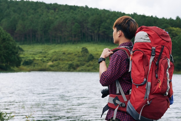 Vue latérale du randonneur avec un grand sac à dos, regardant le lac détourné de la caméra Photo gratuit