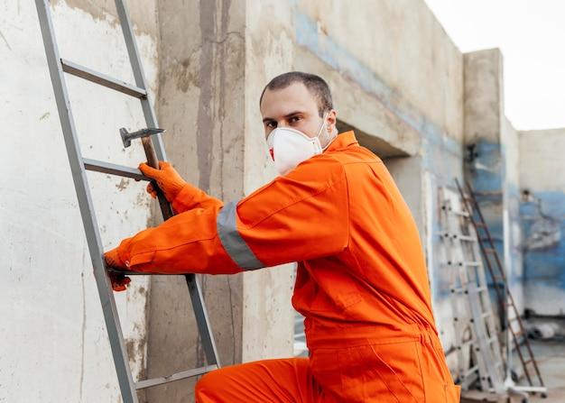 Vue Latérale Du Travailleur Avec Masque De Protection Grimper Sur Une échelle Photo Premium