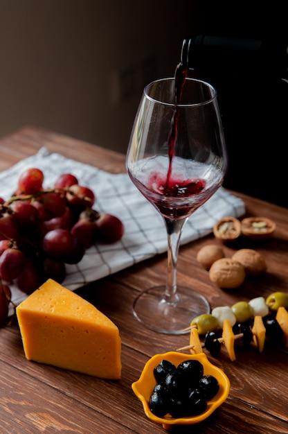 Vue Latérale Du Vin Rouge, Verser Dans Du Verre Avec Du Cheddar Et Du Parmesan, Raisin Olive Et Noix Sur Une Surface En Bois Et Fond Noir Photo gratuit
