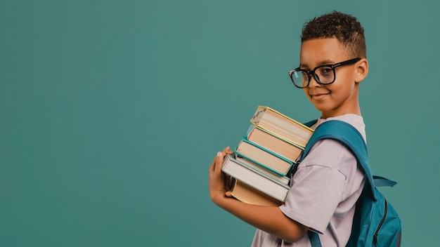 Vue Latérale D'un écolier Tenant Une Pile De Livres Copy Space Photo Premium