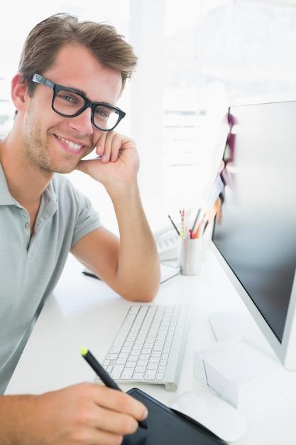 Vue latérale d'un éditeur de photo mâle occasionnel à l'aide de tablette graphique Photo Premium