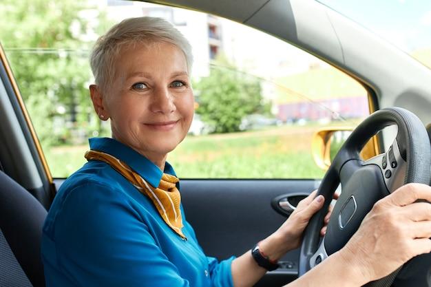 Vue Latérale D'une Femme D'âge Moyen Gaie à L'intérieur De La Voiture Sur Le Siège Du Conducteur Avec Les Mains Sur Le Volant Photo gratuit