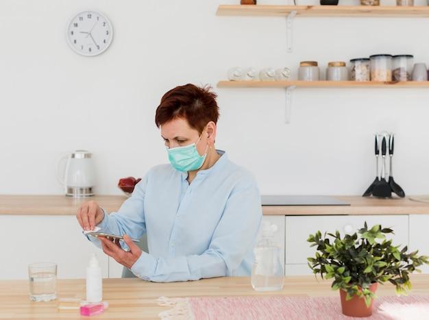 Vue Latérale D'une Femme Aînée Avec Un Masque Médical Désinfectant Son Smartphone Photo gratuit