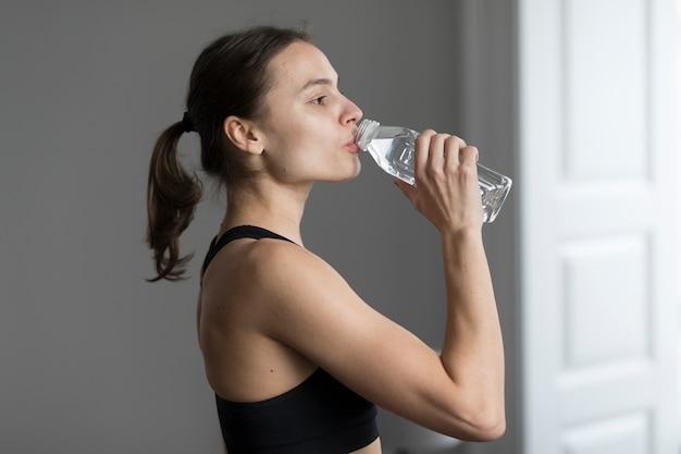Vue Latérale De La Femme Dans L'eau Potable De Vêtements De Sport Photo gratuit