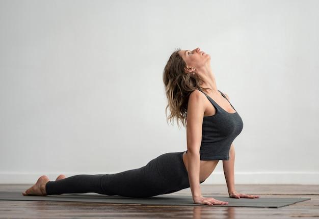 Vue Latérale D'une Femme Faisant Du Yoga à La Maison Avec Espace Copie Photo gratuit