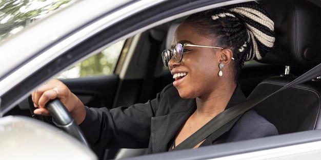 Vue Latérale D'une Femme Heureuse Au Volant De Sa Propre Voiture Photo gratuit