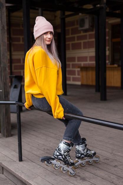 Vue latérale d'une femme avec des patins à roues alignées posant sur une main courante Photo gratuit