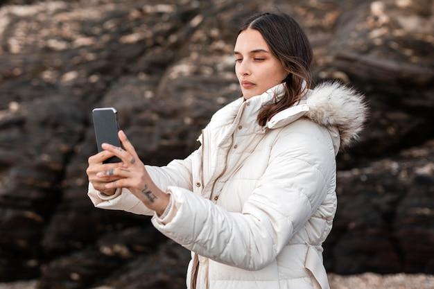 Vue Latérale De La Femme à La Plage à Prendre Des Photos Avec Smartphone Photo gratuit