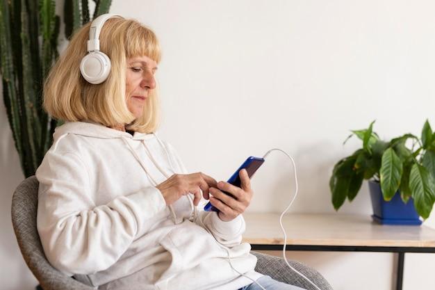 Vue Latérale D'une Femme Plus âgée Avec Un Casque à L'aide De Smartphone Photo Premium