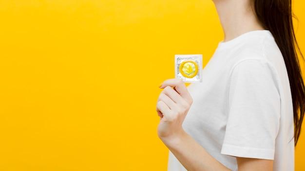 Vue Latérale Femme Tenant Un Préservatif Avec Copie Espace Photo gratuit
