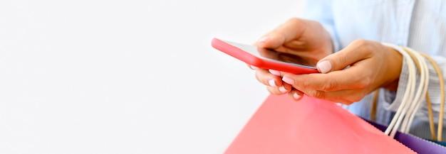 Vue Latérale D'une Femme Tenant Un Smartphone Et Des Sacs à Provisions Pour Cyber Lundi Photo gratuit