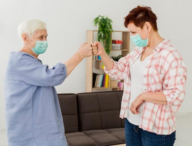 Vue Latérale Des Femmes âgées Avec Des Masques Médicaux Se Cognant Les Poings Pour Se Saluer Mutuellement Photo gratuit