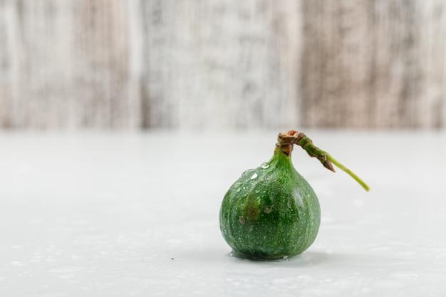 Vue Latérale De Figue Froide Sur Le Mur En Bois Blanc Et Grungy Photo gratuit