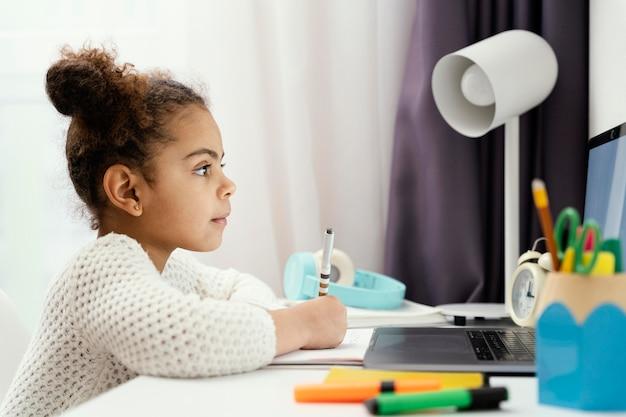Vue Latérale D'une Fille Fréquentant L'école En Ligne à La Maison à L'aide D'un Ordinateur Portable Photo gratuit