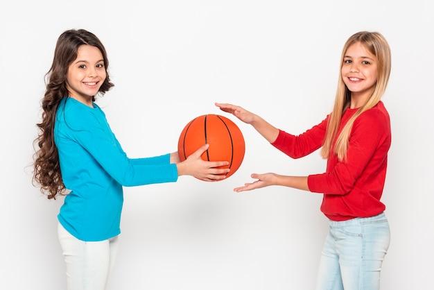 Vue Latérale Des Filles Jouant Avec Un Ballon De Basket Photo gratuit