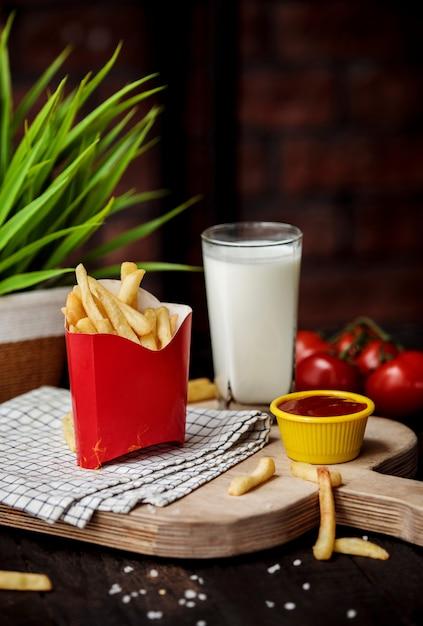 Vue Latérale Des Frites Dans Un Sac En Carton Avec Du Ketchup Sur Une Planche à Découper En Bois Photo gratuit