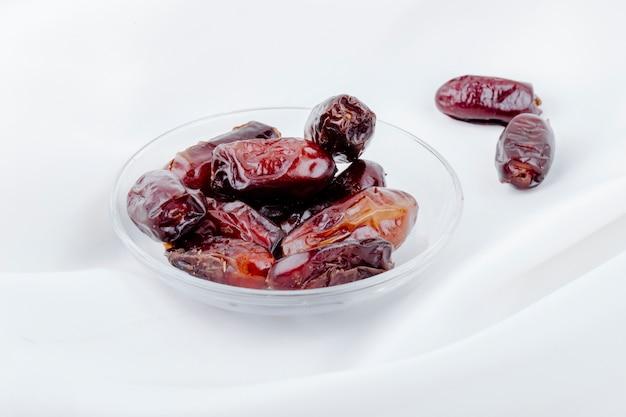 Vue Latérale Des Fruits De Datte Séchés Sucrés Dans Une Soucoupe Sur Fond Blanc Photo gratuit