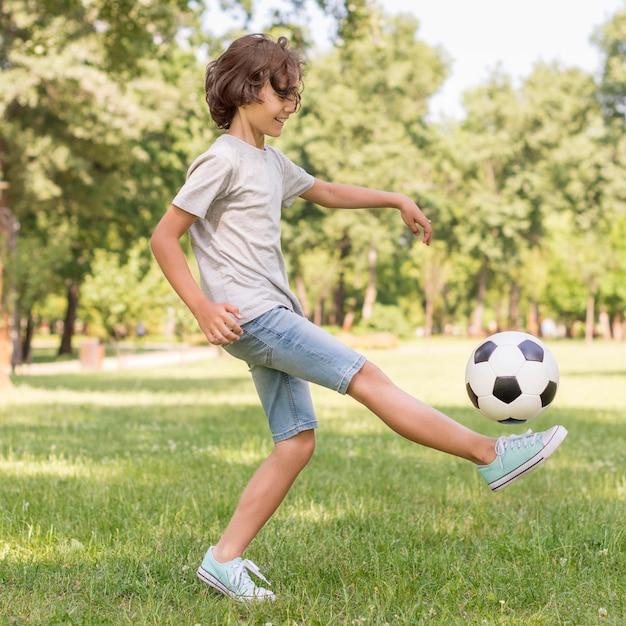 Vue Latérale Garçon Jouant Avec Un Ballon De Football Photo gratuit