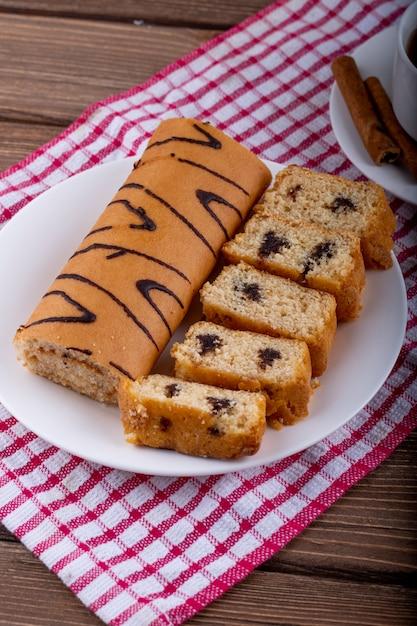 Vue Latérale De Gâteaux éponge Au Chocolat Sur Une Plaque Blanche Servie Avec Une Tasse De Thé Photo gratuit