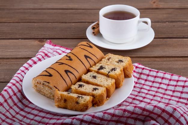 Vue Latérale De Gâteaux éponge Au Chocolat Sur Une Plaque Blanche Et Une Tasse De Thé Sur Bois Photo gratuit
