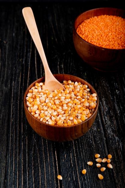 Vue Latérale Des Graines De Maïs Séchées Dans Un Bol Avec Une Cuillère En Bois Sur Une Table Rustique Noire Photo gratuit
