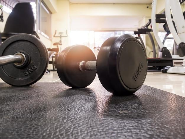 Vue latérale de l'haltère sur le sol dans la salle de fitness Photo Premium