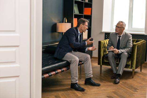 Vue Latérale D'un Homme D'âge Moyen Inquiet Parlant à Son Psychothérapeute Attentif Alors Qu'il était Assis Dans Son Bureau Photo Premium