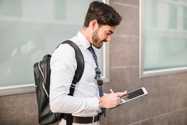 Vue latérale d'un homme à l'aide d'une tablette numérique Photo gratuit