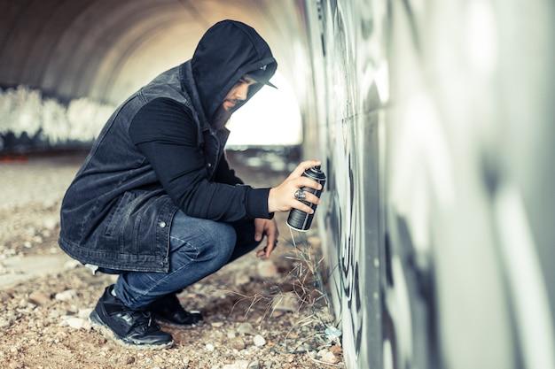 Vue latérale d'un homme à capuche, peinture sur mur de graffitis Photo gratuit