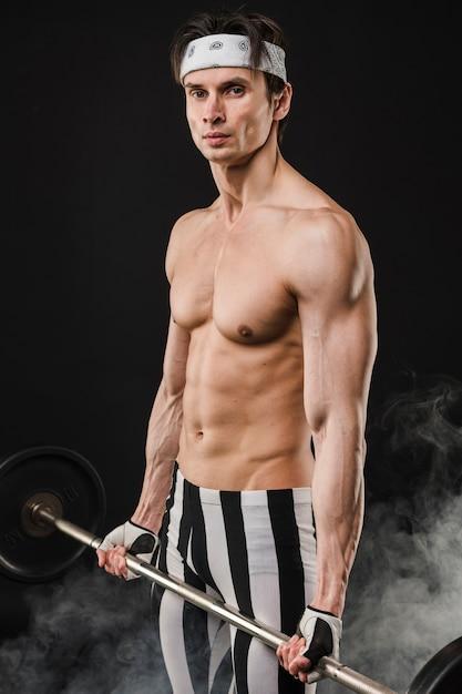 Vue Latérale D'un Homme Musclé Tenant Des Poids Photo gratuit
