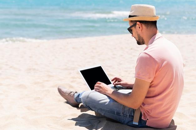 Vue Latérale De L'homme à La Plage Avec Des Lunettes De Soleil Travaillant  Sur Ordinateur Portable | Photo Gratuite