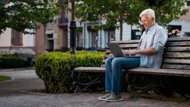Vue Latérale D'un Homme Plus âgé à L'extérieur Sur Un Banc Avec Un Ordinateur Portable Photo Premium