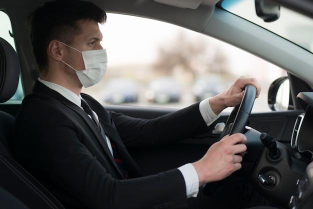 Vue Latérale Homme Portant Un Masque Pendant La Conduite Photo gratuit