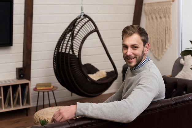 Vue Latérale D'un Homme Posant Sur Un Canapé à La Maison Photo gratuit