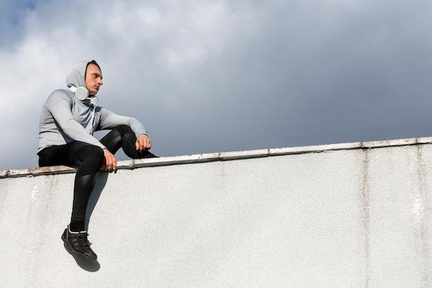 Vue latérale, homme, s'asseoir mur, regarder loin Photo gratuit
