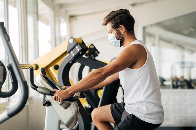 Vue Latérale De L'homme à La Salle De Gym Avec Masque Médical Photo gratuit