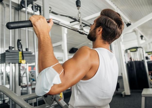 Vue Latérale De L'homme Travaillant Dans La Salle De Sport Avec Masque Médical Sur Son Avant-bras Photo gratuit
