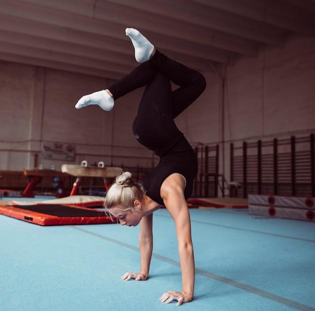 Vue Latérale Jeune Femme Blonde Formation Pour Le Championnat De Gymnastique Photo gratuit