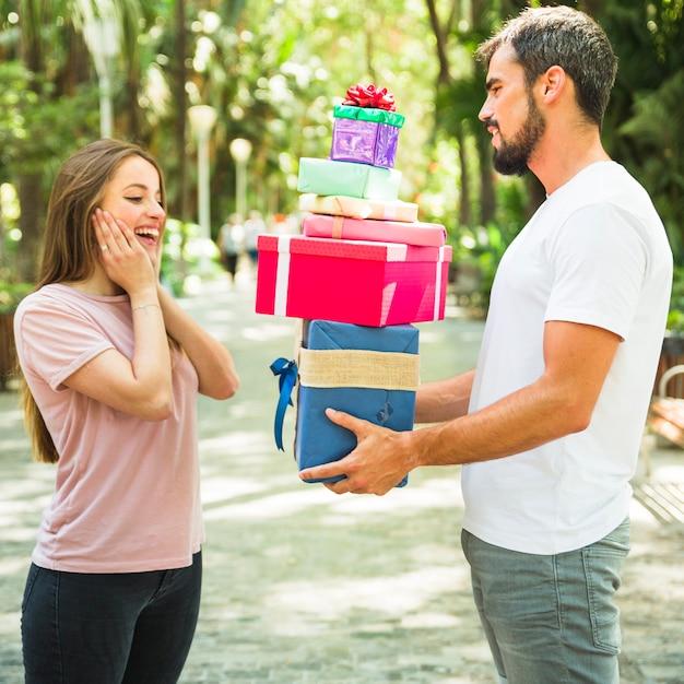 Vue latérale, de, a, jeune homme, donner, pile, de, cadeaux, à, elle, étonné, petite amie Photo gratuit