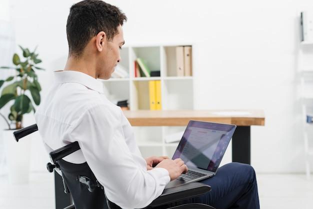 Vue Latérale D'un Jeune Homme Handicapé Assis Sur Un Fauteuil Roulant à L'aide D'un Ordinateur Portable Au Bureau Photo gratuit