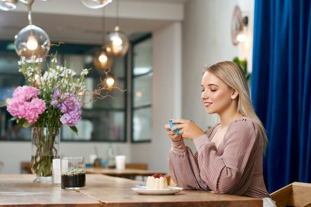 Vue Latérale D'une Jolie Fille Buvant Du Café Dans Un Café Avec Un Intérieur élégant. Photo Premium