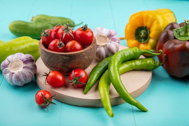 Vue Latérale Des Légumes Comme Bol De Tomate Ail Poivron Sur Une Planche à Découper Avec Des Concombres Sur Bleu Photo gratuit
