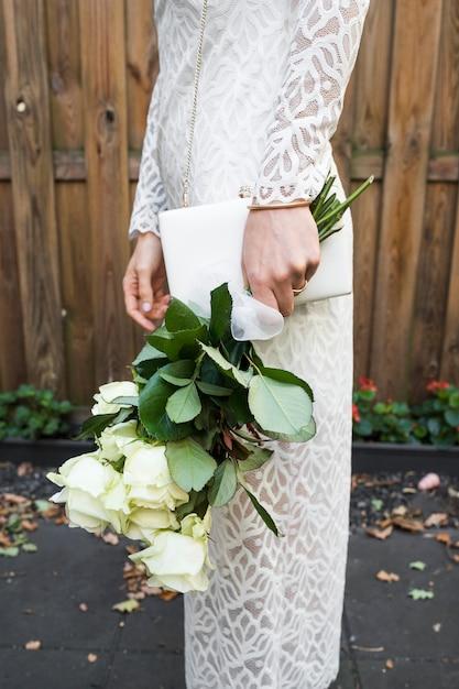Vue latérale de la main de la mariée tenant un bouquet de roses blanches et une pochette Photo gratuit