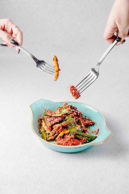 Vue Latérale Des Mains Tenir Des Fourchettes Sur La Plaque Avec Une Salade D'avocat Avec De La Viande Et Du Sésame Photo gratuit