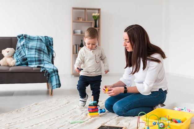 Vue Latérale D'une Maman Jouant Avec Un Enfant à La Maison Photo gratuit
